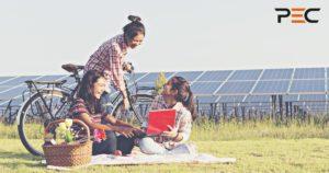 Junge Mädchen mit Laptop sitzend vor Solarmodulen